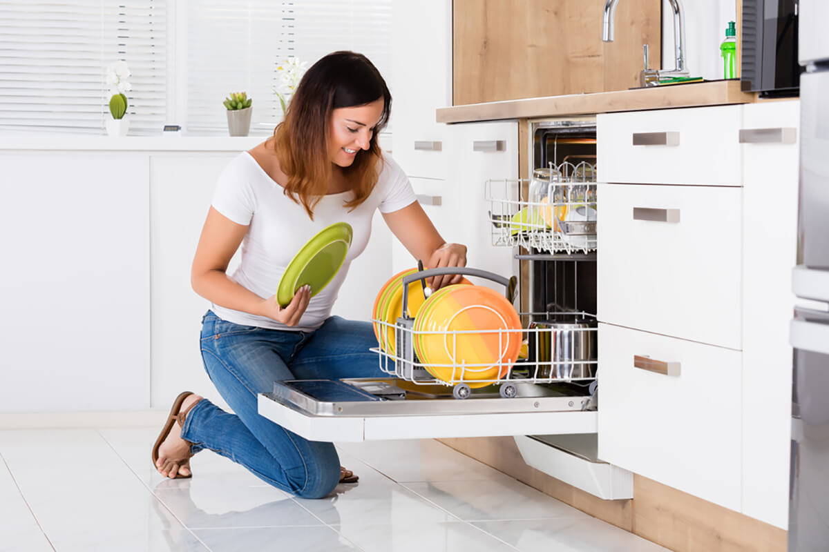 Девушка загружает посудомоечную машину